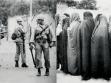 Žena upoutala pozornost šáhovy armády před revolucí, zatímco zahalené ženy se odvrací od muže, po revoluci.